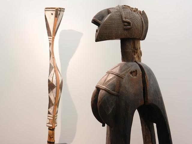 Zwei afrikanische Statuen blicken sich an.