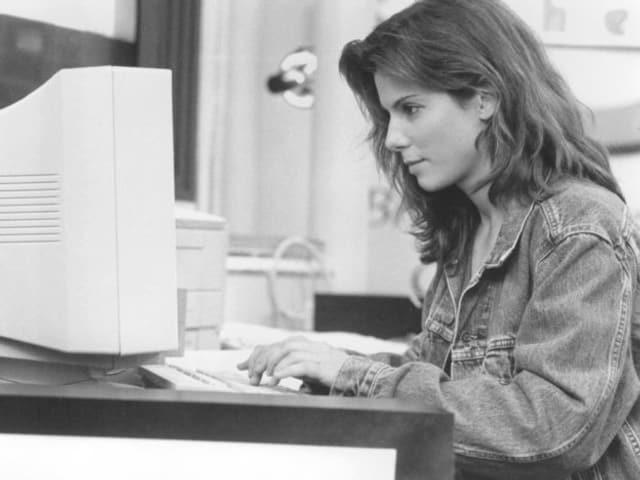 Sandra Bullock sitzt an einem Arbeitsplatz, tippt auf einem Keyboard.