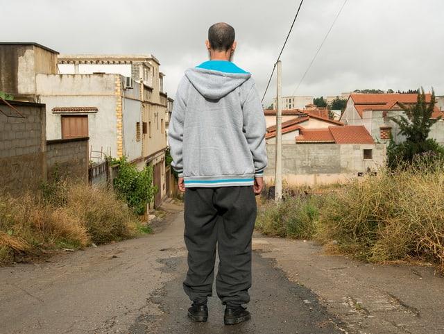 Ein Mann steht mit dem Rücken zur Kamera und schaut auf eine triste Landschaft.