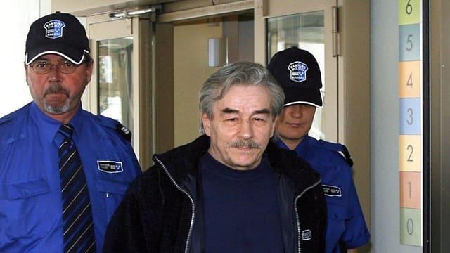 Ein Mann wird von zwei Polizisten begleitet