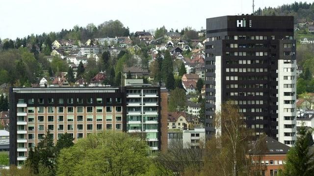 Blick auf zwei GEbäude, im Hintergrund eine Stadt