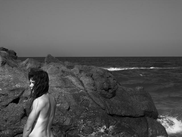 Meer mit Felsenküste, nackte Frau mit dem Rücken zum Betrachter schaut nach links.