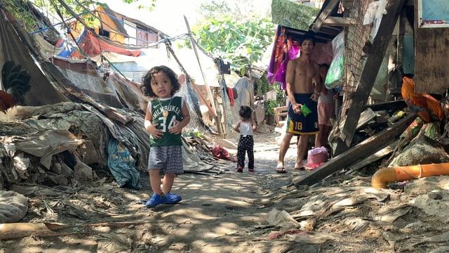 Kinder und zwei Menschen stehen an einem Weg, der voll von Plastik ist.