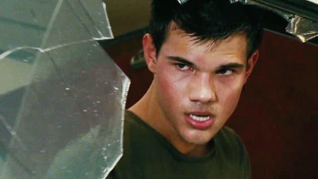 Ein junger Mann blickt zornig durch eine zerbrochene Glasscheibe.