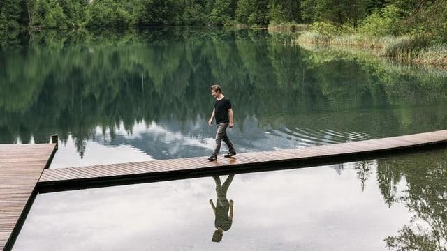 Ein Mann geht über eine Brücke.
