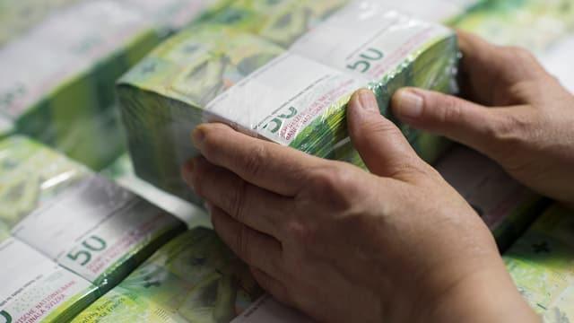 Jemand stapelt zahlreiche Bündel von 50-Franken-Noten.