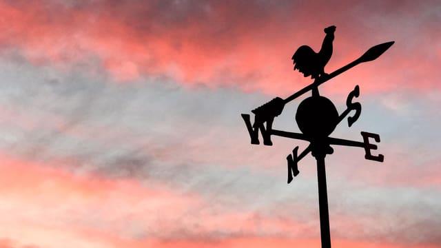 Der Umriss eines Windhahns vor einem rosa Morgenhimmel