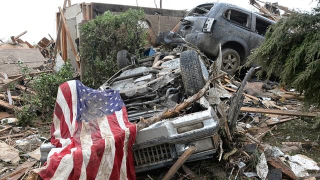 Häuser liegen auf Trümmerhaufen. Im Vordergrund eine US-Flagge.