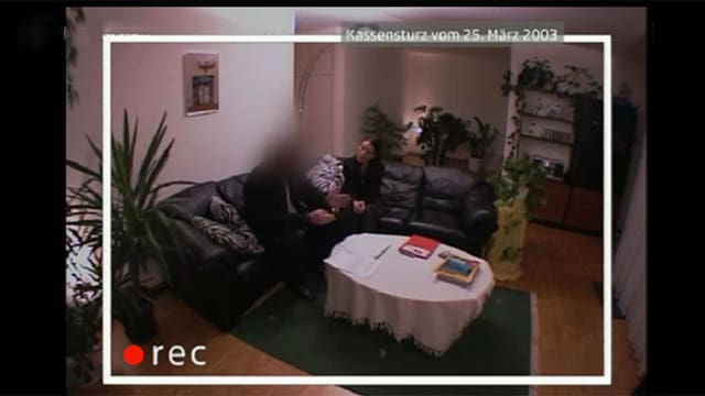 EIn Mann und eine Frau in einem Wohnzimmer aus der Sicht einer vertseckten Kamera.