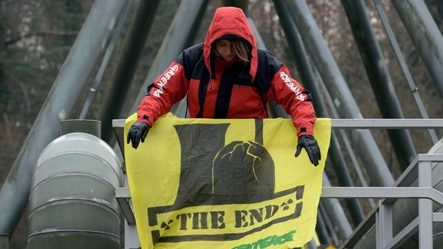 Eine Aktivistin montiert in luftiger Höhe ein gelbes Transparent mit der Aufschrift «The End».