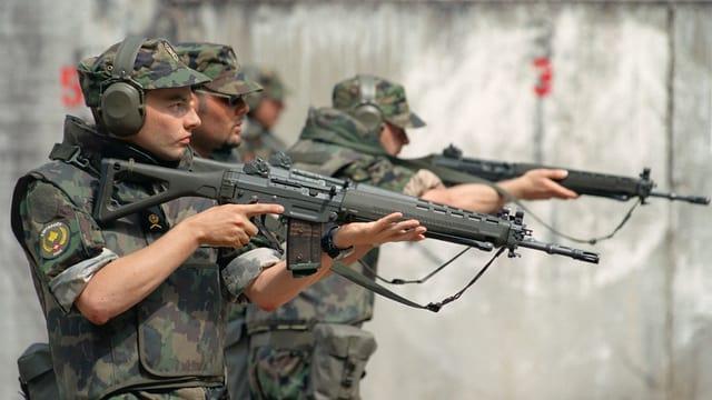 Purtret da militarists svizzers che sajettan cun armas.