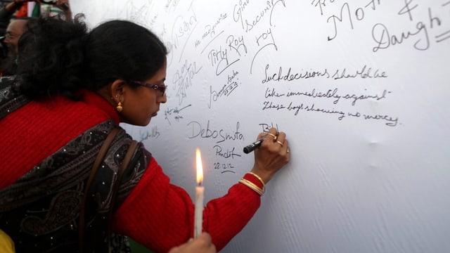 Eine Frau schreibt auf eine weisse Wand