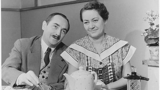 Ruedi Walter und Margrit Rainer sitzen am mit Kaffeekrug und -tassen gedeckten Tisch.
