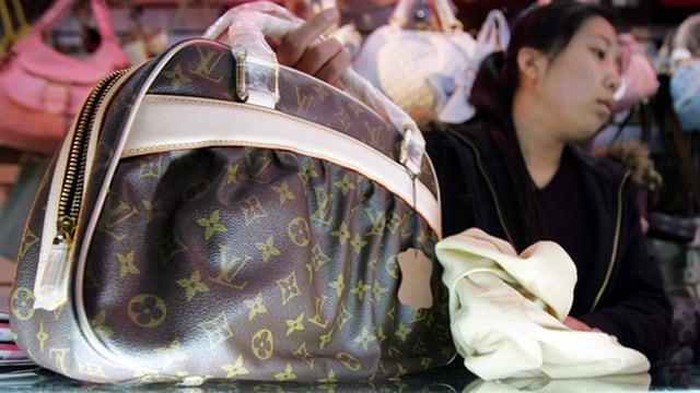 Chinesische Verkäuferin bietet eine gefälschte Louis-Vuitton-Tasche an