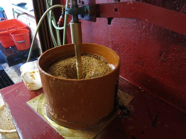 In einem Topf sind die zerquetschten Früchte. Sie werden nun durch eine Maschine durch ein Sieb gepresst.