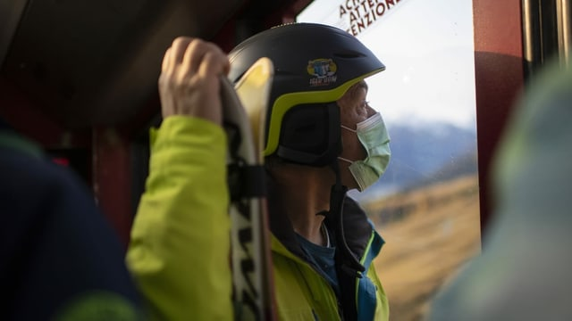 Man mit Ski in Seilbahn