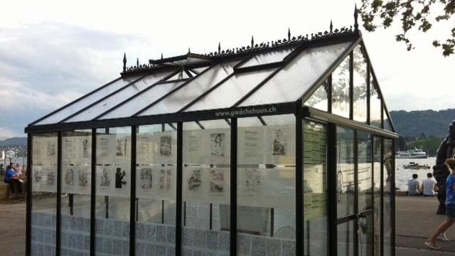 Ein Glashaus, an den Wänden hängen Zeitungsausschnitte.
