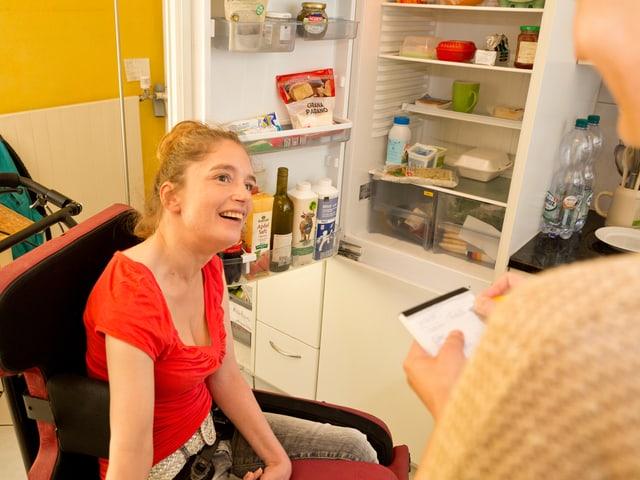 Eine behinderte Frau im Rollstuhl vor einem Kühlschrank. Eine Frau mit einer Liste.
