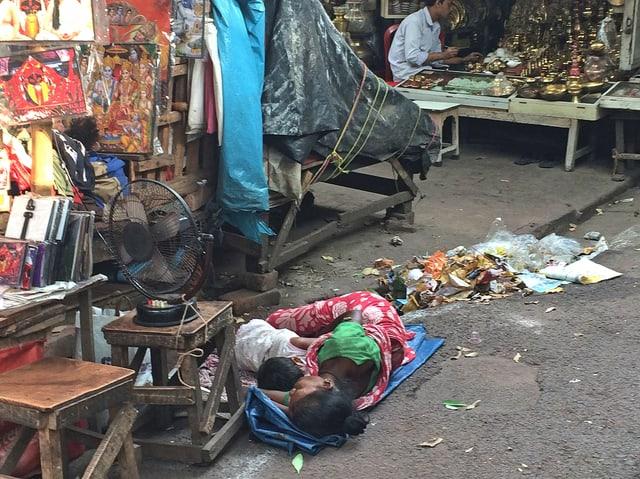 Menschen schlafen auf einer dünnen Matte am Strassenrand
