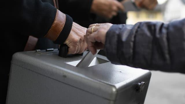 Urna da votaziu e maun che bitta en cedels.