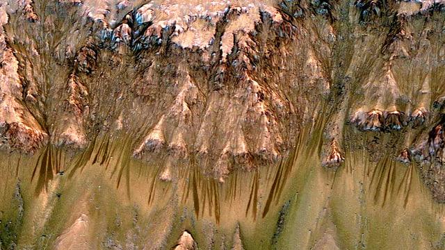 Bergflanke auf dem Mars. Abfallend daran sind Rillen zu sehen, die auf die zumindest sporadische Gegenwart von flüssigem Wasser hindeuten.