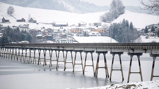 Ein Viadukt über einen See, am andern Ufer ein Dorf.