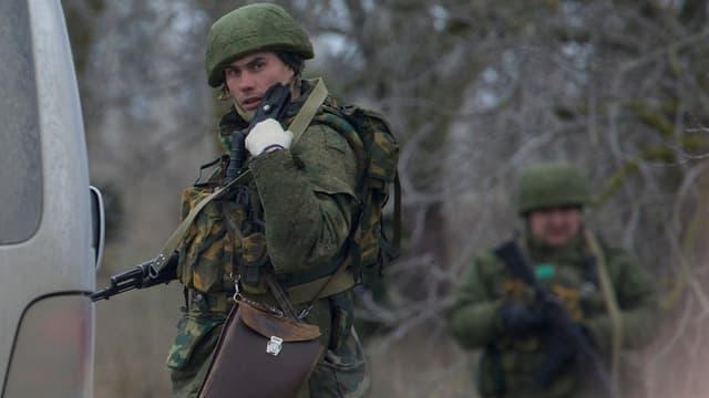 Soldat im Vordergrund spricht in ein Funkgerät