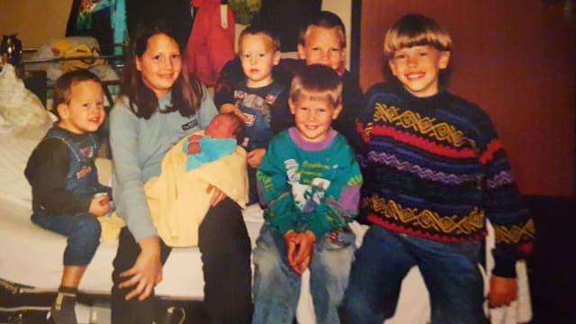 Kindheitsfoto: Daniela Oberholzer und ihre sieben Brüder sitzen auf einem Bett