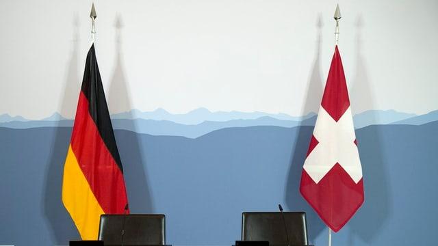 Leere Stühle vor einer Schweizer und einer Deutschen Flagge.