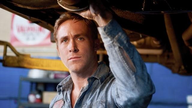 Ryan Gosling steht unter einem Fahrzeug.