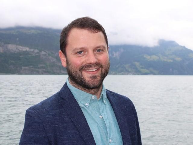 Porträtbild eines jungen Mannes mit Bart und blauem Veston - im Hintergrund ist der See.