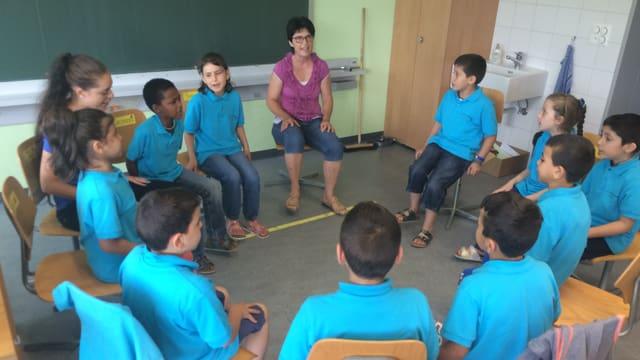 Syrische Kinder sitzen in einem Kreis und lernen Deutsch.