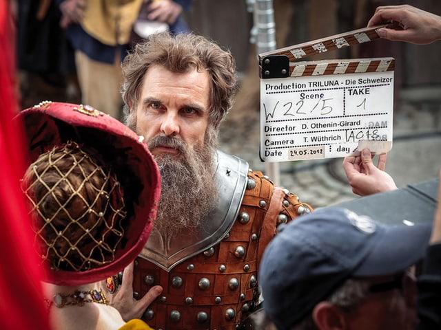 Ein Mann mit Bart, davor eine Filmklappe.