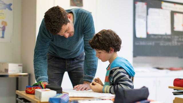 Ein Primarlehrer erklärt einem Schüler eine Aufgabe.