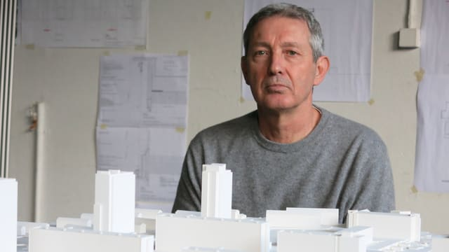 Porträt Rolf Mühlethaler vor einem Modell des Quartiers Tscharnergut.