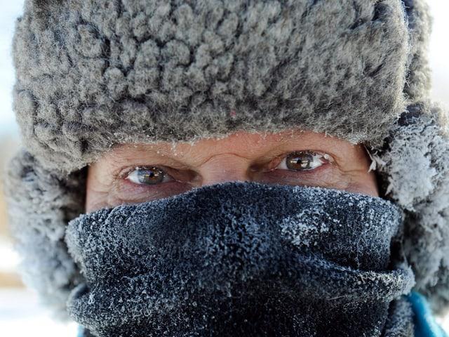 Mann mit Fellmütze auf dem Kopf und Schal vor dem Gesicht.