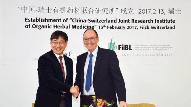 Zwei Männer geben sich die Hand, im Hintergrund chinesische und englische Schrift an der Wand