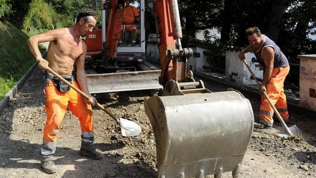 Zwei Männer arbeiten mit Schaufeln und Bagger an einer Strasse.