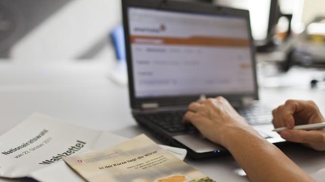Ein Laptopbildschirm zeigt die Webseite von Smartvote, daneben liegen Wahlunterlagen.