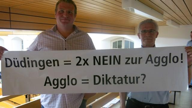 Düdinger Alt-Agglorat Werner Wyss und SVP-Präsident Stefan Siegenthaler mit Protestplakat.