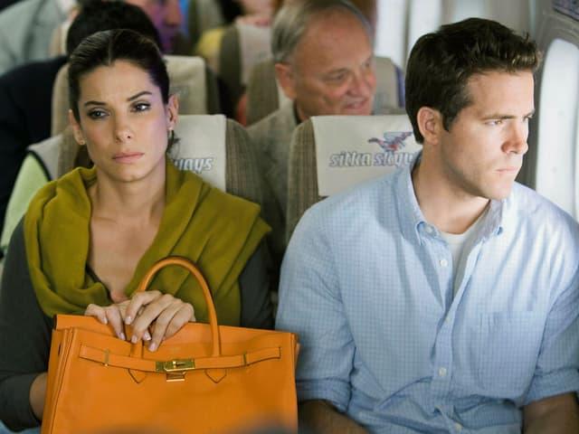 Sandra Bullock und Ryan Reynolds sitzen verstimmt nebeneinander im Flugzeug und starren in die Leere.