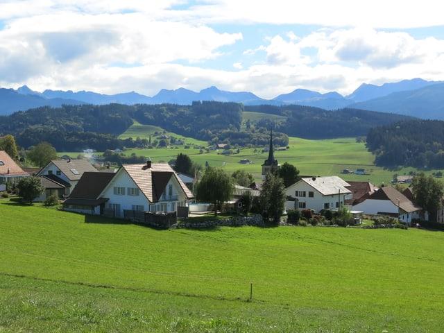 Grüne Wiese, blauer Himmel, dazwischen Häuser und Kirche.