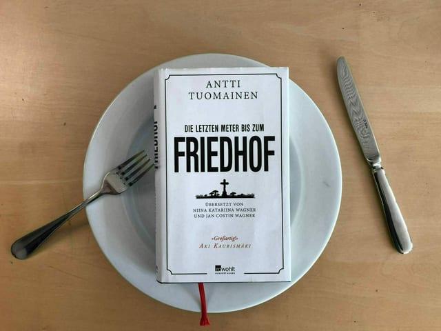 Das Buch «Die letzten Meter bis zum Friedhof»  von Antti Tuomainen liegt auf einem weissen Teller. Messer und Gabel liegen hingeworfen daneben.