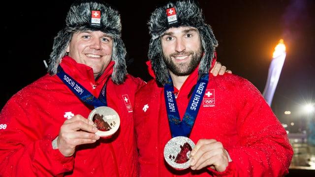 Beat Hefti (links) und Alex Baumann tragen wärmende Mützen und zeigen ihre Medaillen.