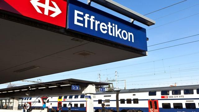 Das Bahnhofschild von Effretikon, dahinter eine S-Bahn.