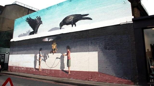 Wandmalerei: Seilspringende Kinder. Darüber ein Dach mit einem Loch. Darauf sitzen zwei Krähen und schauen durch das Loch.