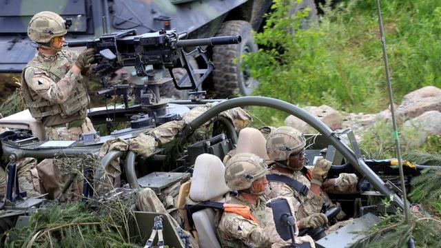 Nato-Soldaten mit Maschinengewehr auf einem Jeep.