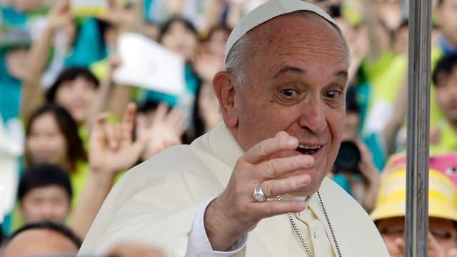 Papst Franziskus nimmt in einem offenen Wagen ein Bad in der Menge und winkt.