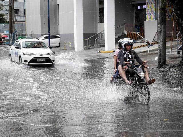 Mann fährt mit Töff durchs Wasser.