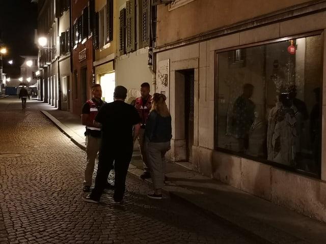Vier Personen in einer Seitengasse einer Altstadt.